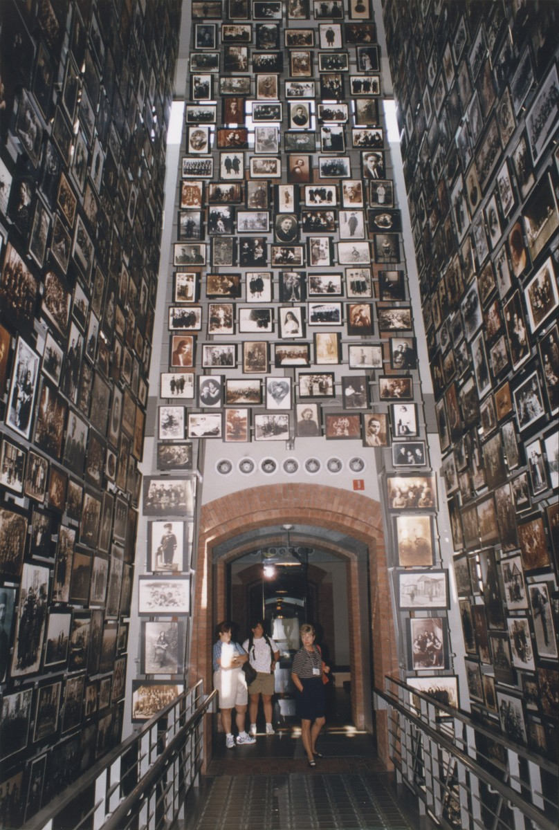 Visitors view the Tower of Faces (Yaffa Eliach Shtetl Collection) in the permanent exhibition of the U.S. Holocaust Memorial Museum.