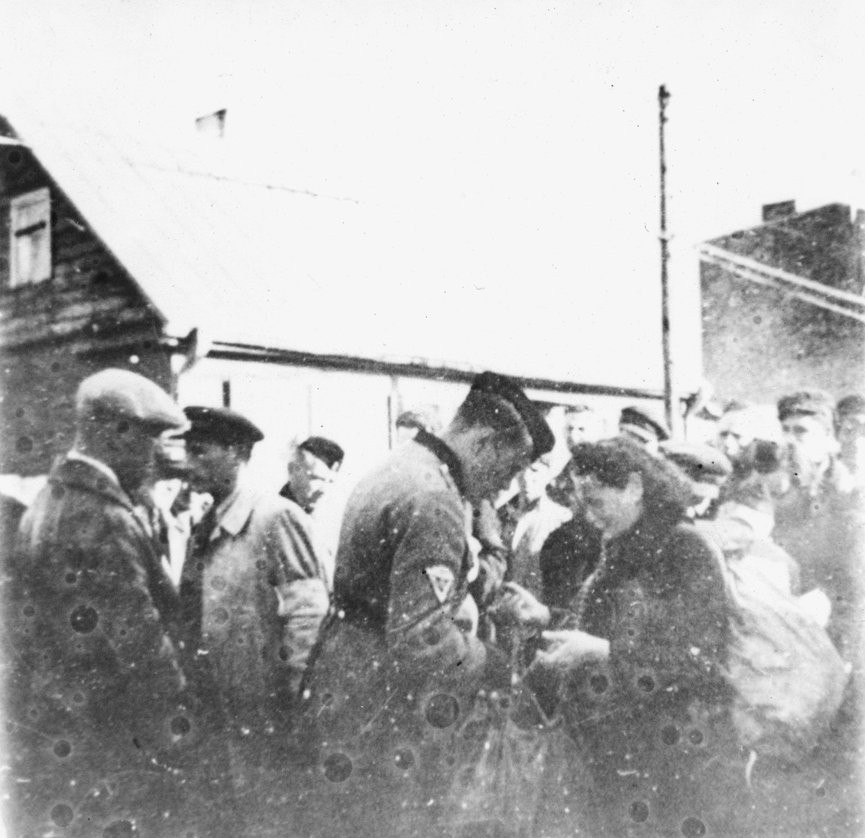 Kovno workers are searched by ghetto police at the Krisciukaicio Street entrance upon their return from forced labor outside the ghetto.