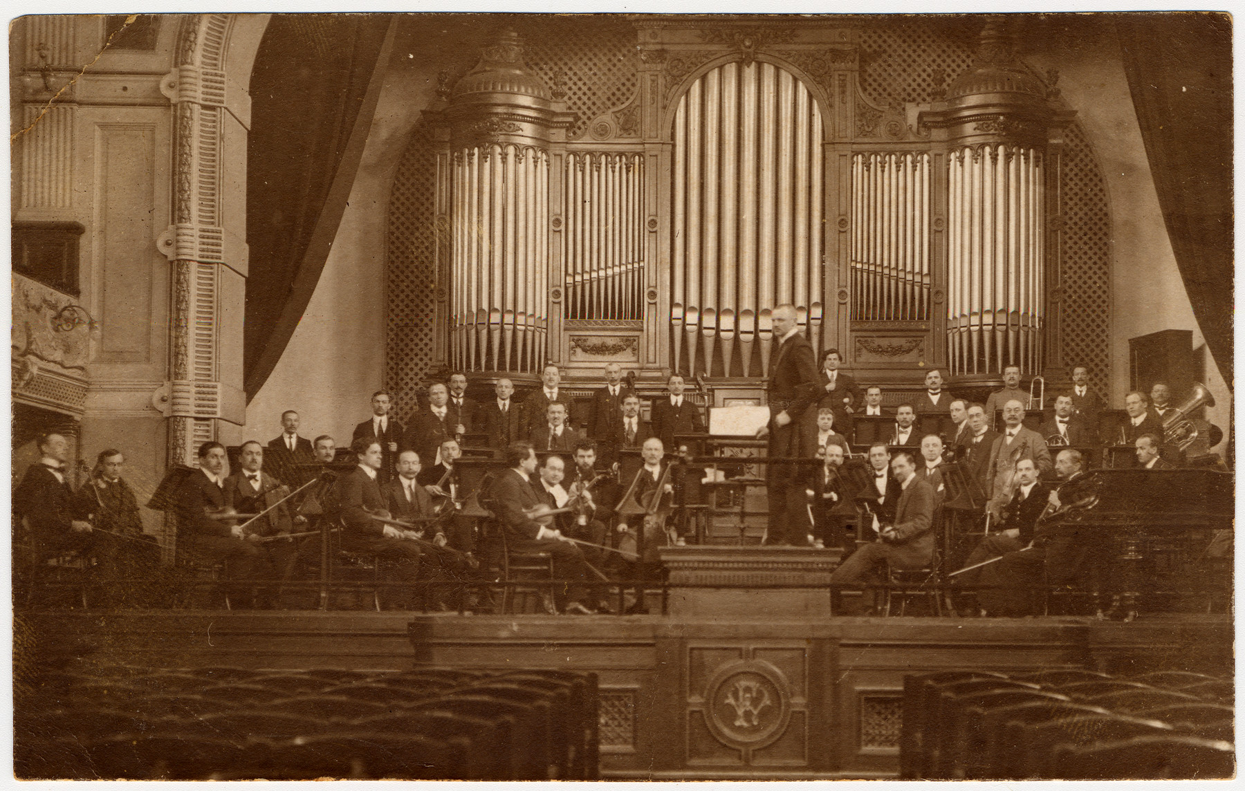 Members of a Polish symphony, including many Jewish musicians, pose on stage with their instruments.