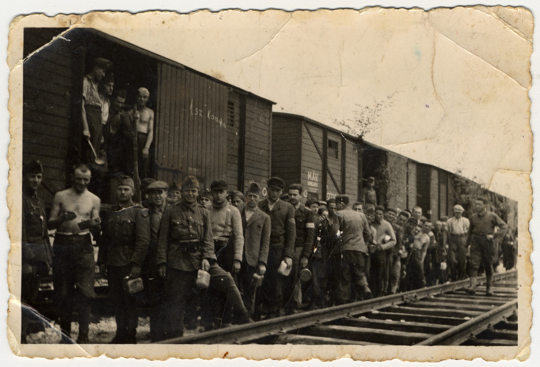 Jewish men in a  Hungarian forced labor battalion stand inside and along side a train.