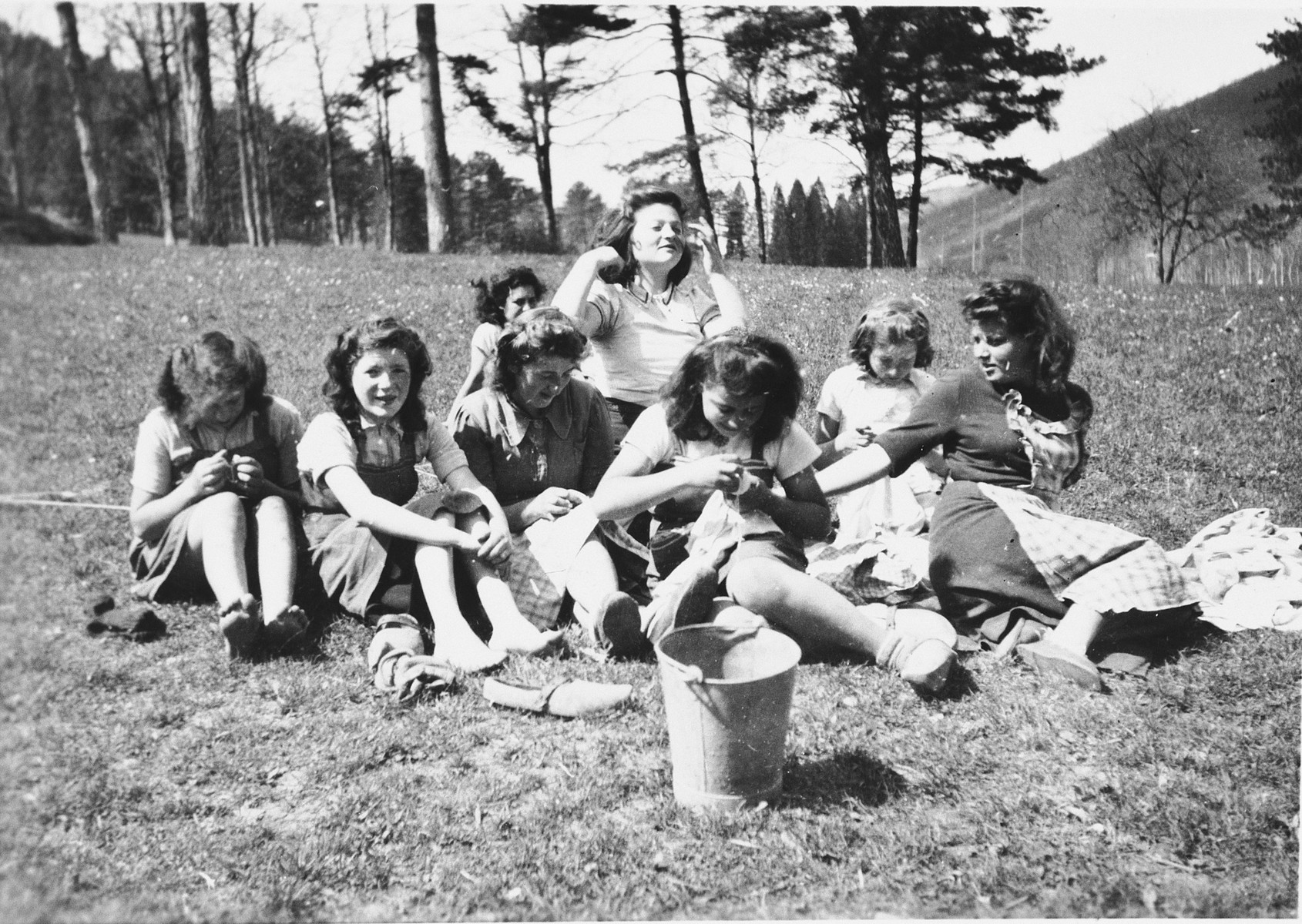 Girls sit on the grounds of La Hille and sew.  Second from left, Irene Kokotek (now Nathan); to her right, possibly Irma Seelenfreund; center rear with hands up, Martha Storosum; far right in dark dress, Gerti Lind.