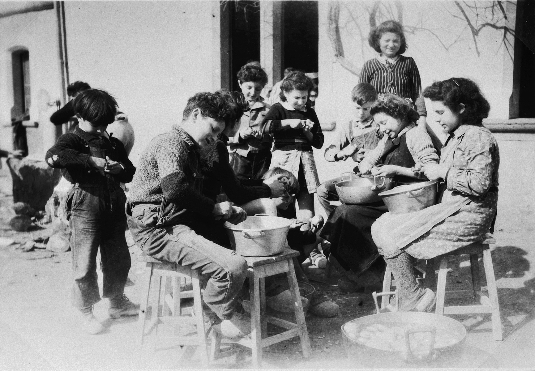 Children peel potatoes under the supervision of female staff at the Chateau La Hille.   The boy at left front is Jojo (a French boy).  Next to him, facing to the right, is Paul Schlesinger. Above his head, to the right, Peter Bergmann. To his right, peeling potatoes, in dark sweater, probably is Friedel  Kriegstein (now Schula Wald); standing in rear, Martha Storosum.