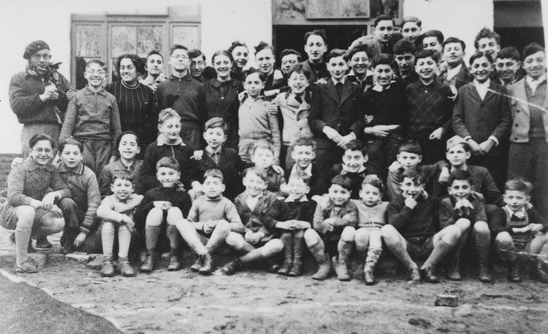 "Group portrait of the children who came to Belgium from Germany and Austria on a Kindertransport outside the Speyer children's home at 128 rue Victor Rauter in Anderlecht.  Front row (left to right): Guy Haas, Georges Herz, Willy Wolpert (?), Alfred Eschwege. Martin Findling. Manfred Tidor, Henri Vos, Gerhard Eckmann, unknown, and Fred Findling.  Second row: Gerard Kwaczkowski. Manfred Vos, Egon Berlin, Rudi Oehlbaum, unknown, Bernard Eisler, unknown, Joseph Dortort, Max Krolik, and Klaus Sostheim.  Back row: Mr. Becker, Willy Grossmann, female counselor, Gerd Obersitzker, Leo Grossmann, Emile Dortort, Tante Lucienne DeWaay, unknown, Peter Salz, Edgar Chaim, Manfred Kamlet, unknown, Bertrand Elkan, Hans Garfunkel. Lucien Wolfgang. unknown, Henri Brunel. Werner Rindsberg, Jacques Roth, Norbert Stueckler, Kurt ""Onze"" Klein, and Norbert Winter.  Far back are Charles Blumenfeld, and Eddie Nussbaum."