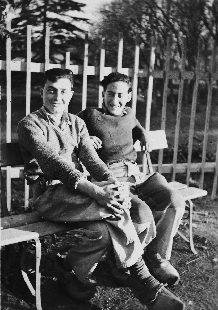 Two older youth sit on a bench on the grounds of Chateau de la Hille.  Pictured are Kurt Klein and Joseph Dortort.