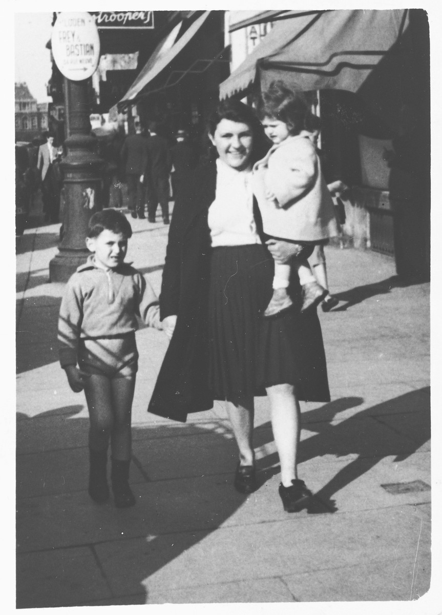 Georges and Myriam Abramowicz go for a walk with their maid down a street in Brussels.