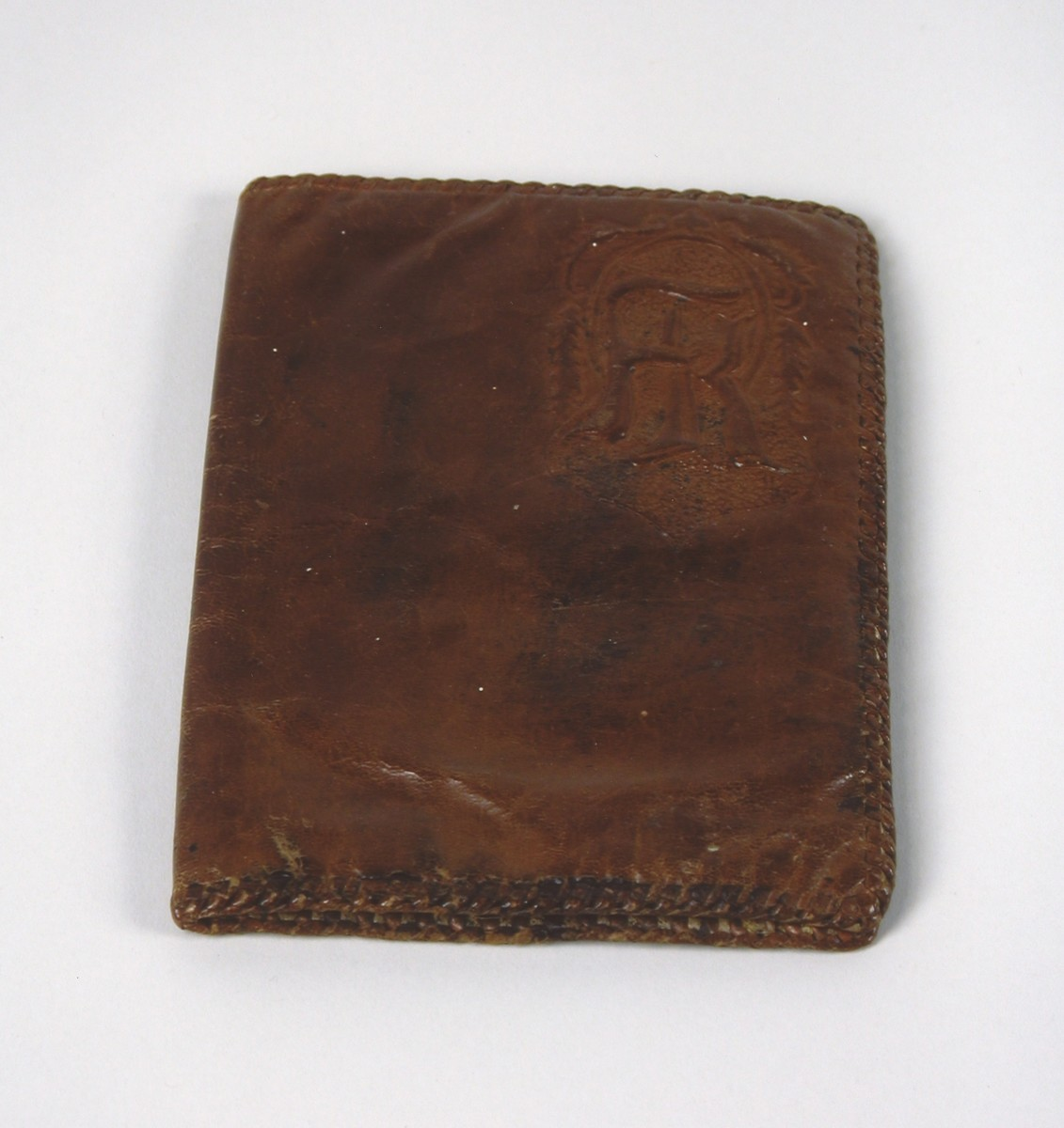 A brown, leather-tooled folio belonging to the Gondos family, who took it with them when they left Budapest aboard the Kasztner rescue train.  Anna Ilona Gondas made this and other hand-tooled leather objects during the war to supplement the family income while her husband was serving in the Hungarian Labor Service.  The monogram suggests that this was a custom-made item that the owner never took possession of.