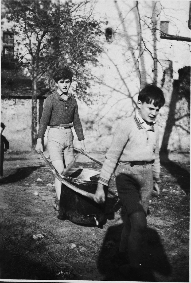 Two children carry water to the Chateau de la Hille.  Pictured are Georges Herz (left) and Fernand Nohr (right).
