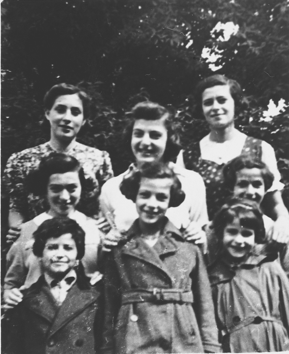 Portrait of eight Jewish refugee girls in the garden of the children's home in Zuen.  Pictured include Rosalie Blau (now Johnson), Toni Rosenblatt, Ruth Rosenblatt, Regina Rosenblatt, Lotte Nussbaum, Inge Joseph and Edith Goldapper (now Rosenthal).
