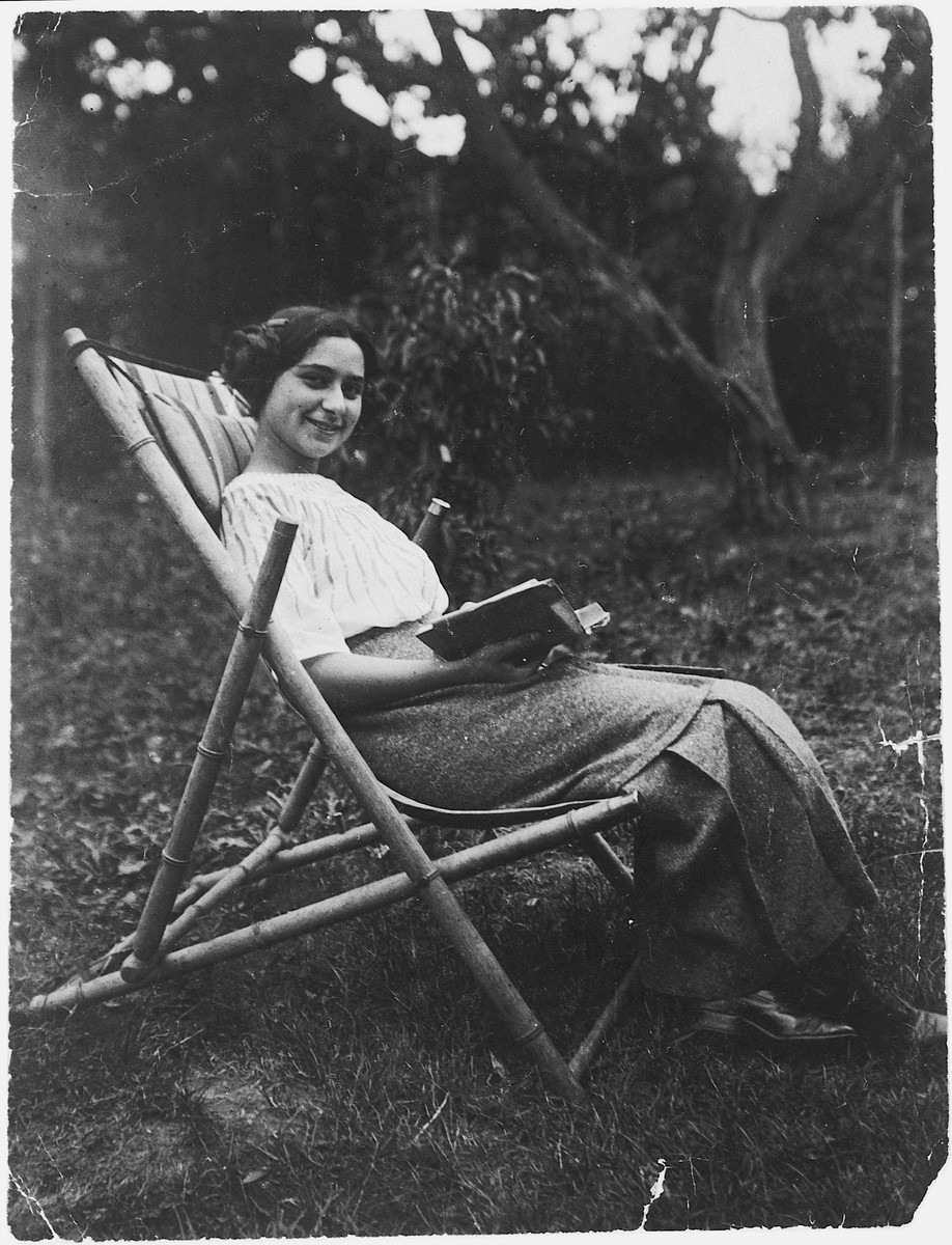 Jolan Deutsch poses with a book on an outdoor lounge chair.