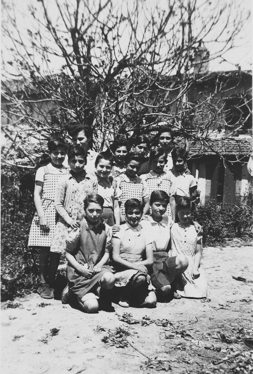 """Group portrait of girls in the """"Moyennes"""" (middle group) in the children's home in Seyre.  First row (left to right): Eva Kantor, unidentified, Martha Storosum, and unidentified.  Second row: unidentified, Trude Dessauer, Betty Schuetz, Fanny Kuhlberg, Lore Flanter, and unidentified.  Back row: Ruth Schuetz, Rita Kuhlberg, Gerti Lind and Frieda Rosenfeld."""