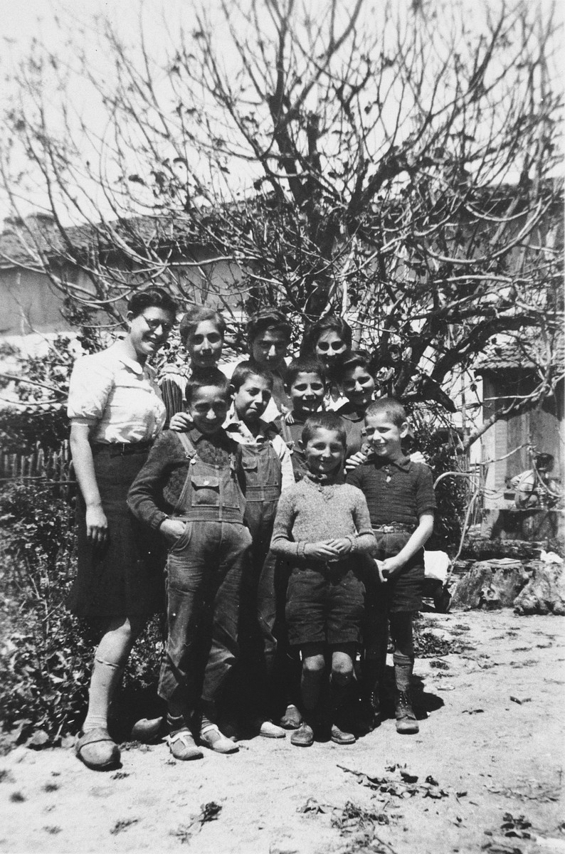 """""""Les Moyens"""" (the middle group) boys pose with the older girls in the children's home in Seyre.  First row (left to right): Gerhard Eckmann, Guy Haas, Paul Schlesinger, Peter Bergmann, and Siegfried Findling.  Back row: Edith Goldapper, Lotte Nussbaum, Inge Joseph, Ruth Klonover and Adele Hochberger."""