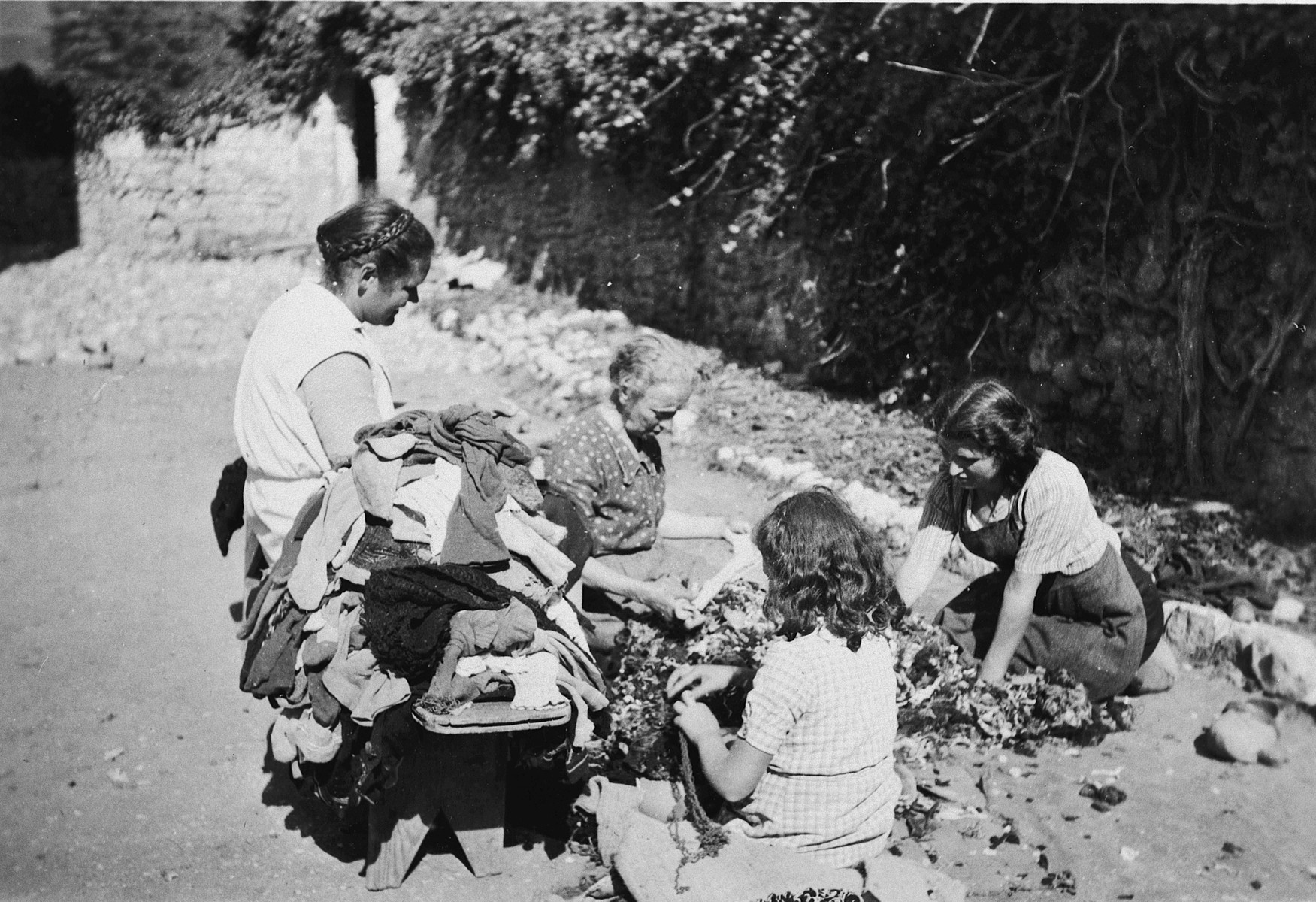 Female staff sort and repair clothing at the Chateau La Hille.  The older woman in the center is Madam Nadal.