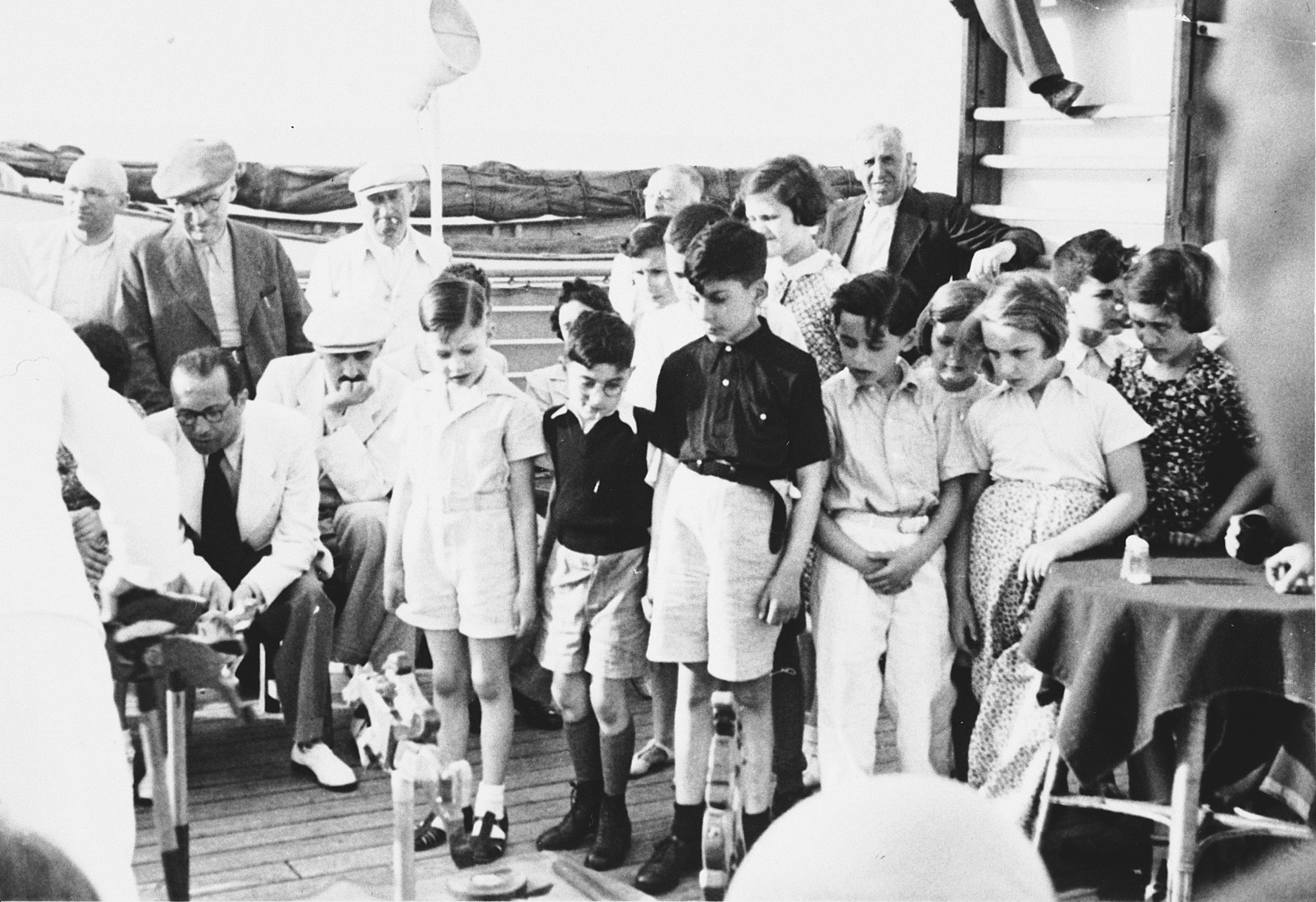 A group of children observe a game on the deck of the St. Louis.  Jan Chraplewski is the first child on the left.