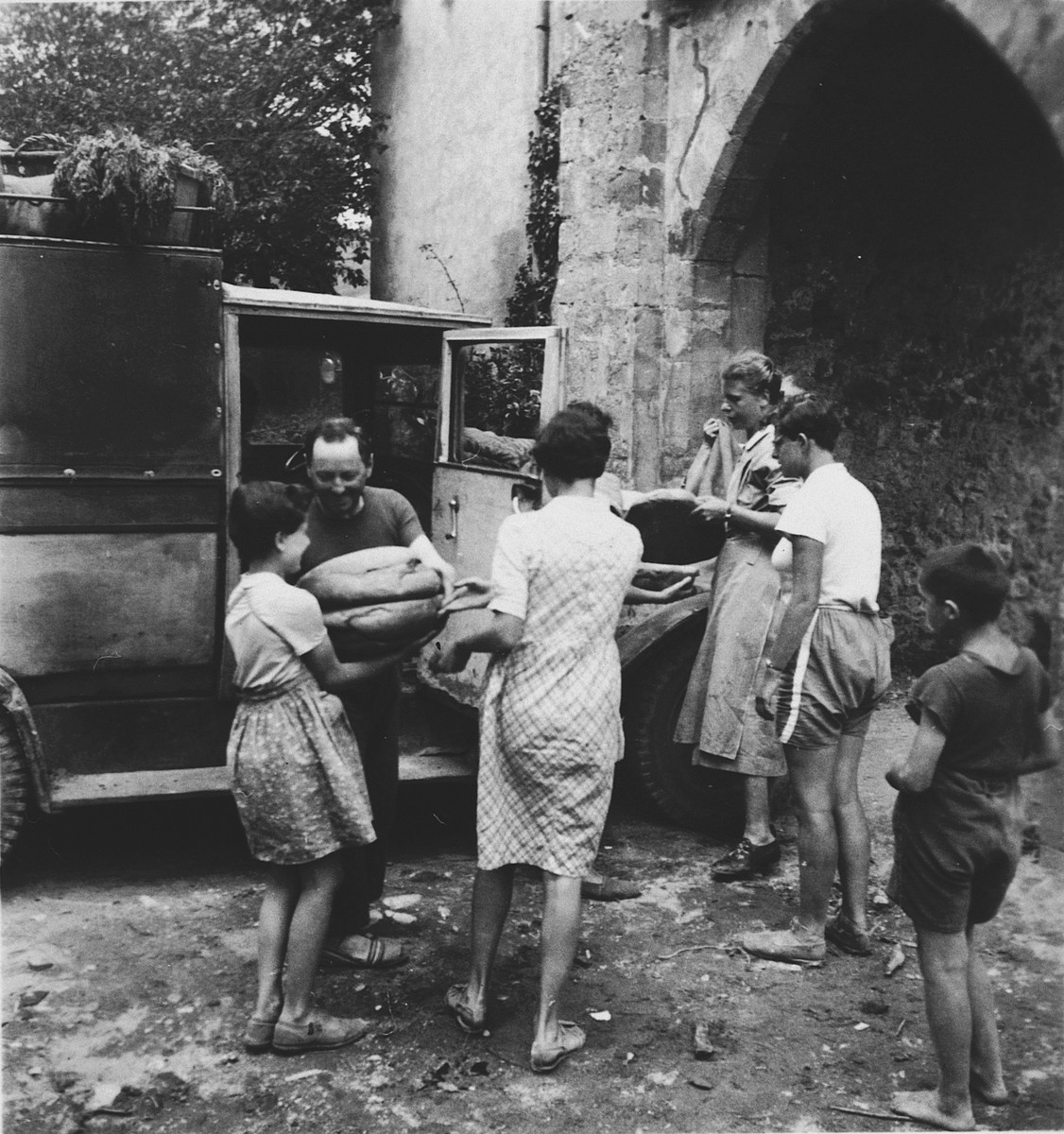 Children help unload bread being delivered to the Chateau La Hille.  Edith Goldapper (later Rosenthal) is pictured at the far right.  Roesli Naef is pictured third from the right (with a wrist watch on her left arm).  Gerhard Eckmann may also be pictured.