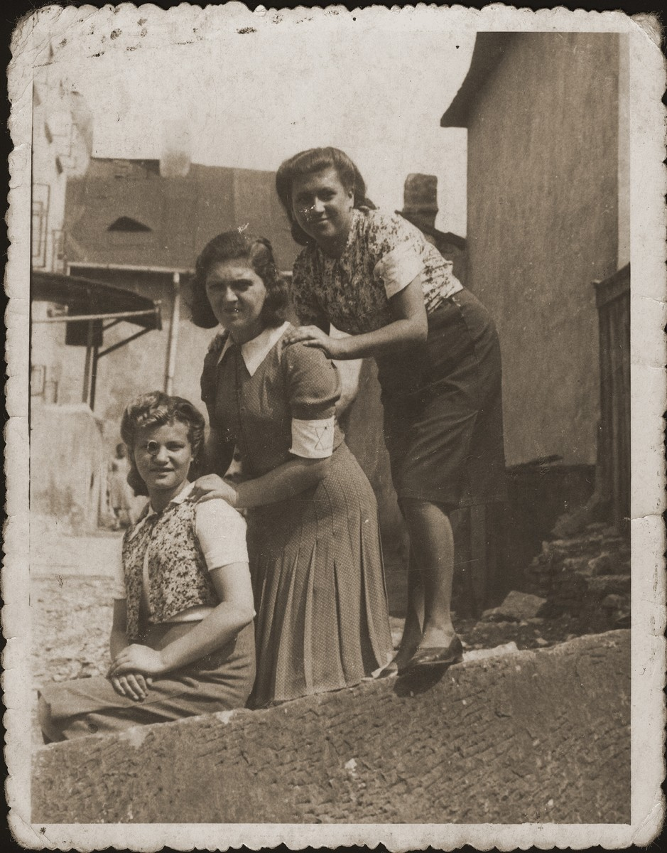 Three young Jewish friends pose outside wearing armbands in the Bedzin ghetto.  Pictured are Janka Najer (now Jennie Wolerman), her cousin, Dorka Londner, and an unnamed friend.