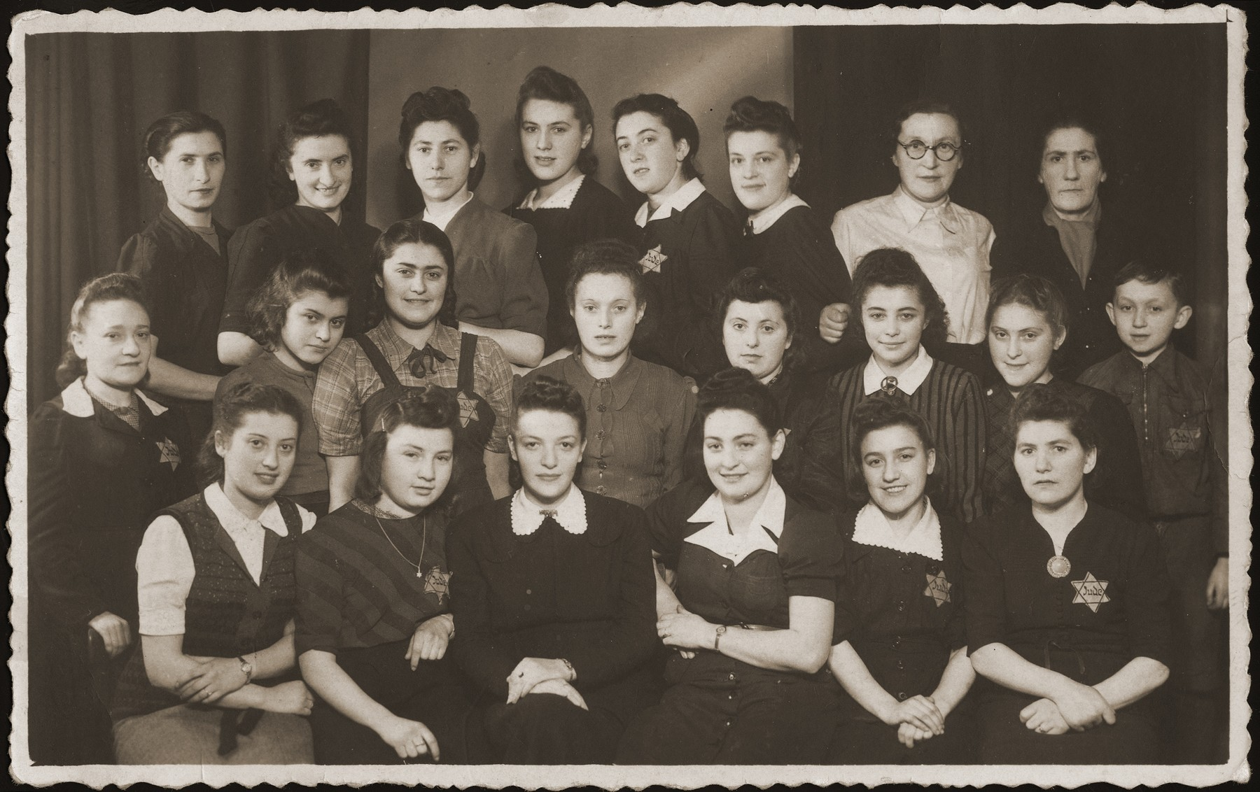 Group portrait of young women wearing Jewish badges, who worked in a sewing workshop in Bedzin.    The donor, Ruzia Grinbaum is pictured in the front row, third from the right.  The little boy, standing in the middle row at the far right, was hidden in the workshop by his mother, who is seated directly in front of him.  Of the entire group, only the donor survived the war.