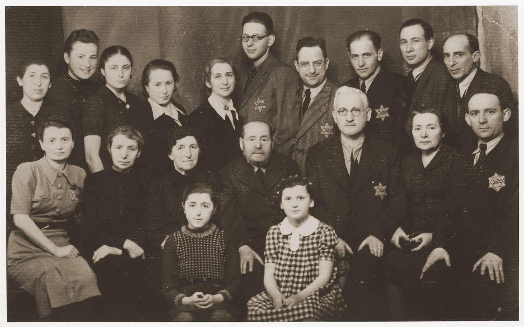 Group portrait of members of the Buchwajc and Laskier families in the Bedzin ghetto.    Among those pictured is Hala Buchwajc (top row, second from the left), Chana Laskier (top row, fifth from the left), Yehuda Laskier (top row, sixth from the left, Chana's son), Michal Laskier (top row, seventh from the left, Chana's husband), Ida Buchwajc (front row, second from the right, Hala's mother), and Pinkus Buchwajc (third from the right, Hala's father). The Laskiers survived the war in the Tittmoning international internment camp.  They were able to leave Bedzin on South American passports secured for them by their relative, Alfred Schwartzbaum, in Switzerland.