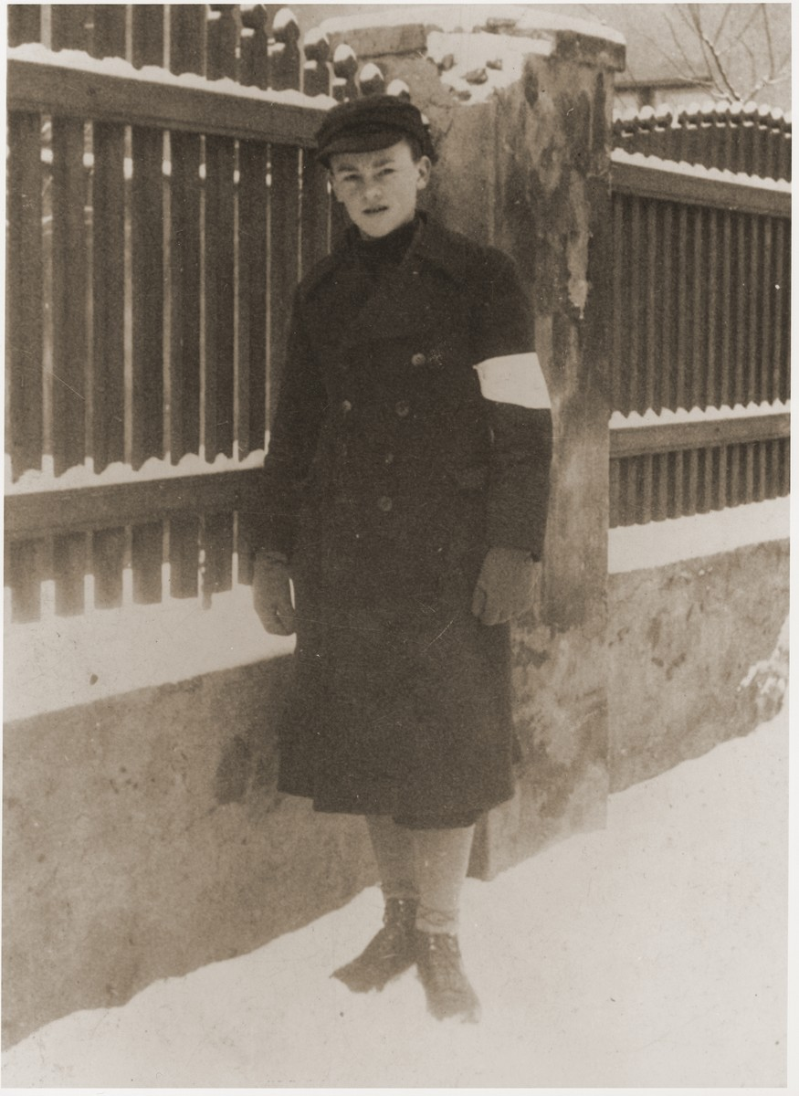 14- year-old Zygmunt Baum poses wearing an armband on a snow-covered street in the Bedzin ghetto.    His overcoat is part of his Furstenberg gymnasium school uniform, but the shiny buttons had to be removed on orders of the German authorities, in order to distinguish it from a military uniform.  This photograph was sent in 1940 to the family in the U.S.