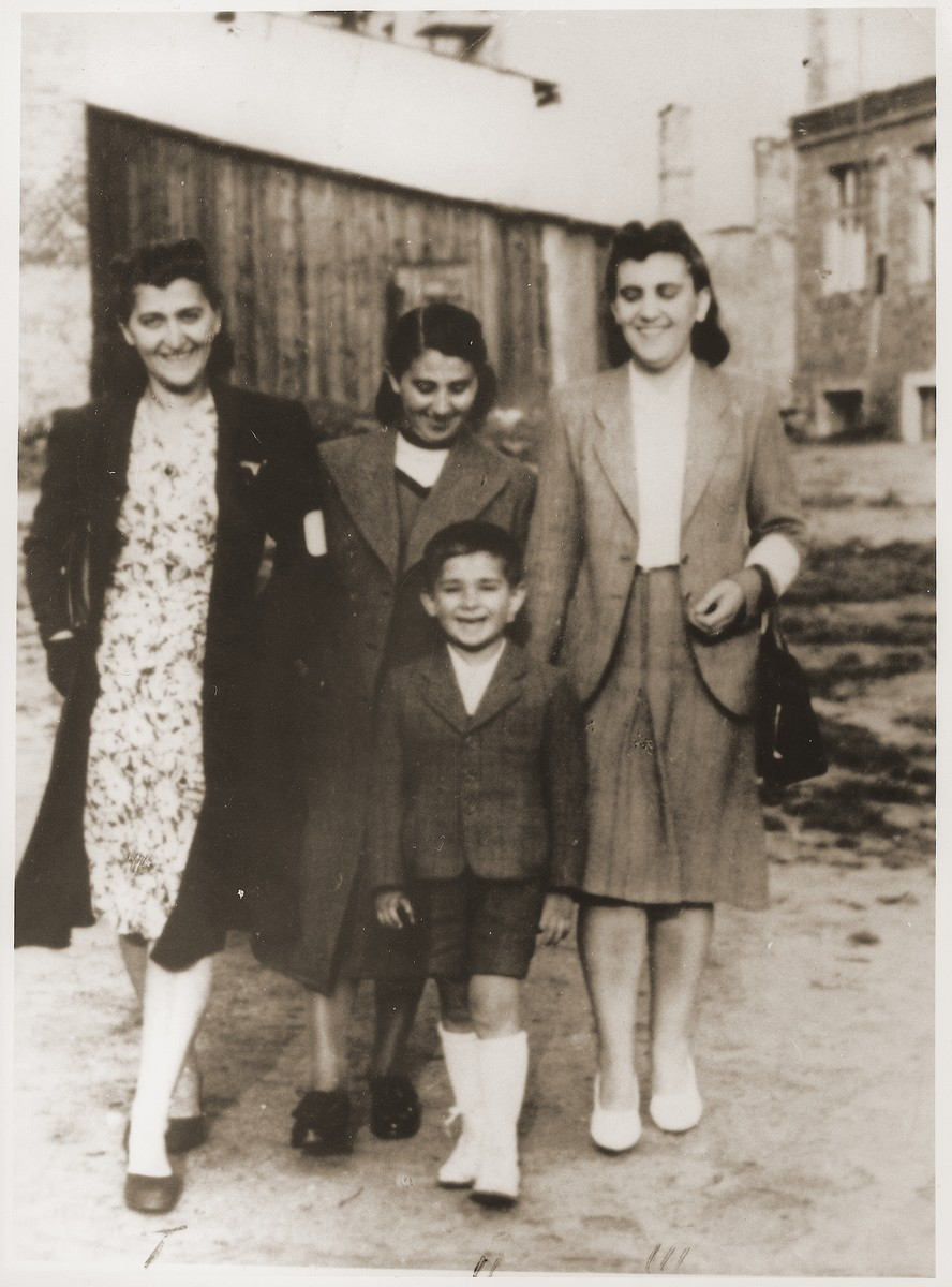 Members of the Oppenheim family pose outside wearing armbands in the Bedzin ghetto.  Among those pictured is Hela (Oppenheim) Erlich (at the right), her sister, Bronka (Oppenheim) Laskier (at the left), and their youngest sister (name unknown, in the middle).  Bronka's son stands in front.  Hela (Oppenheim) Erlich was the first wife of the donor's husband, Mejer Erlich.