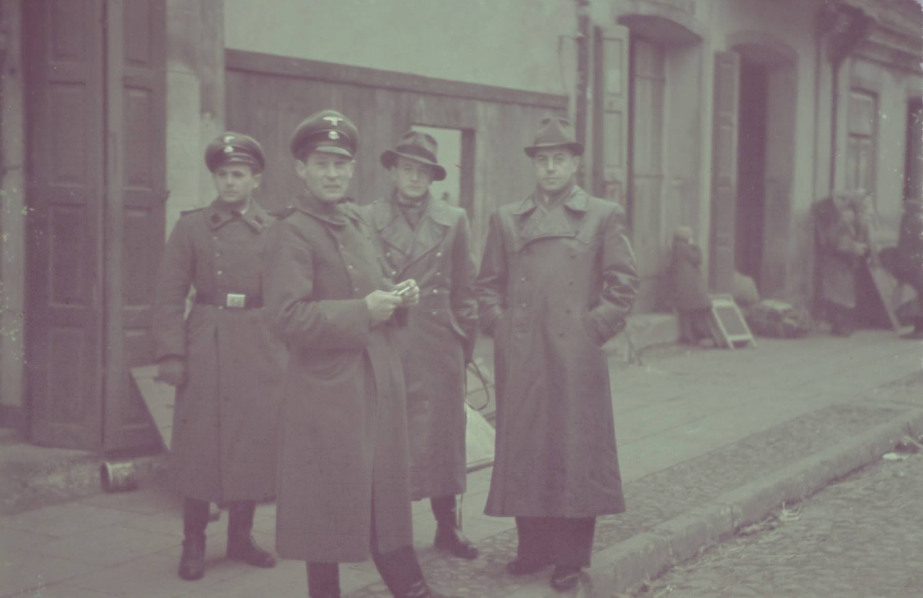 Two SS men gather with two other Germans on a street in the Lodz ghetto.