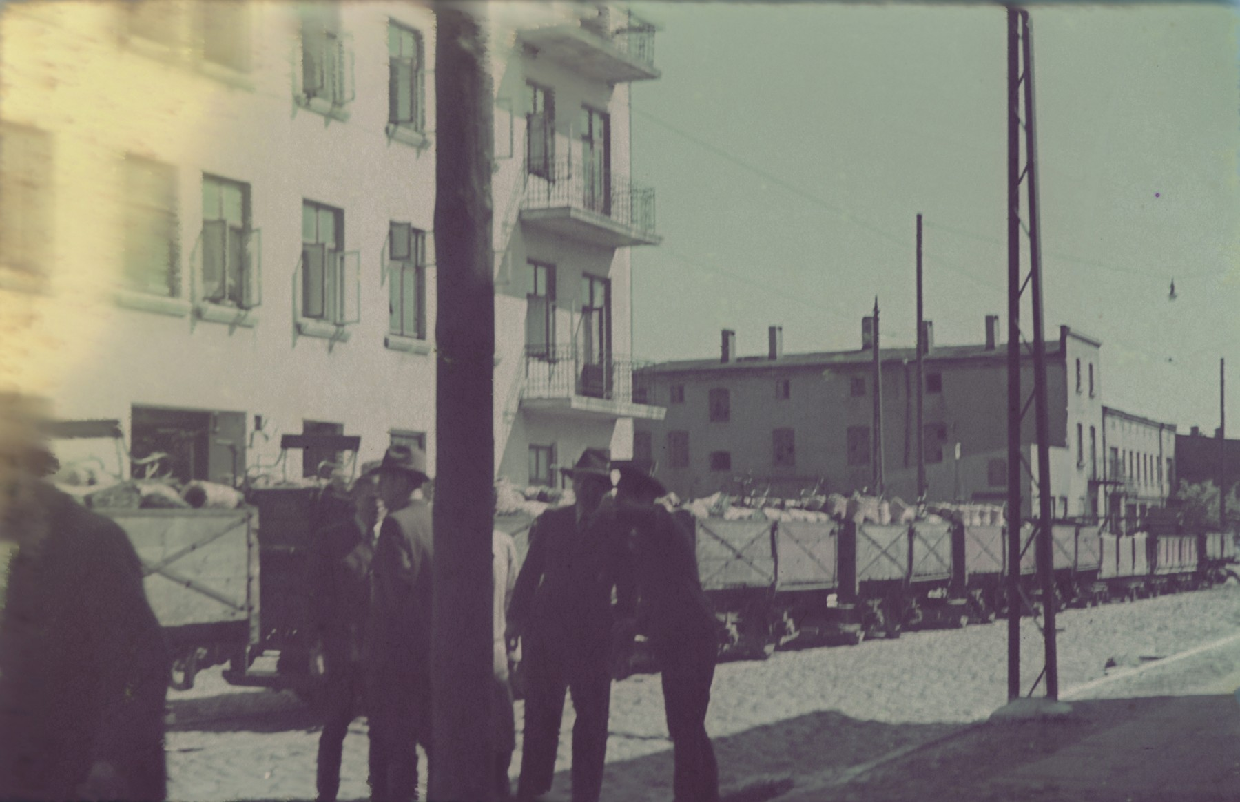 """A train filled with coils of straw for the shoe factory travels through a street of the Lodz ghetto.  Original German caption: """"Litzmannstadt-Getto, Strohschufabrik"""" (straw show factory), #199."""