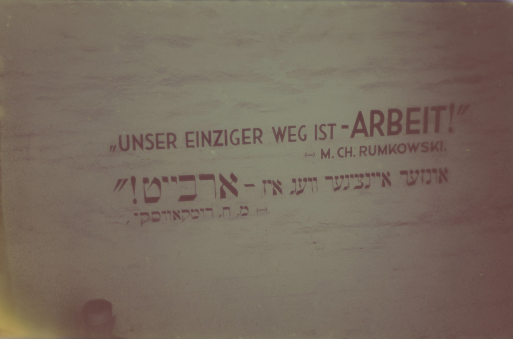 "A sign bearing the motto of Mordechai Chaim Rumkowski: ""Our only path [to survival] is [through] work!"" in German and Yiddish.  Original German caption: ""Litzmannstadt-Getto, Aufschrift in ??"" (inscription on a ??)"