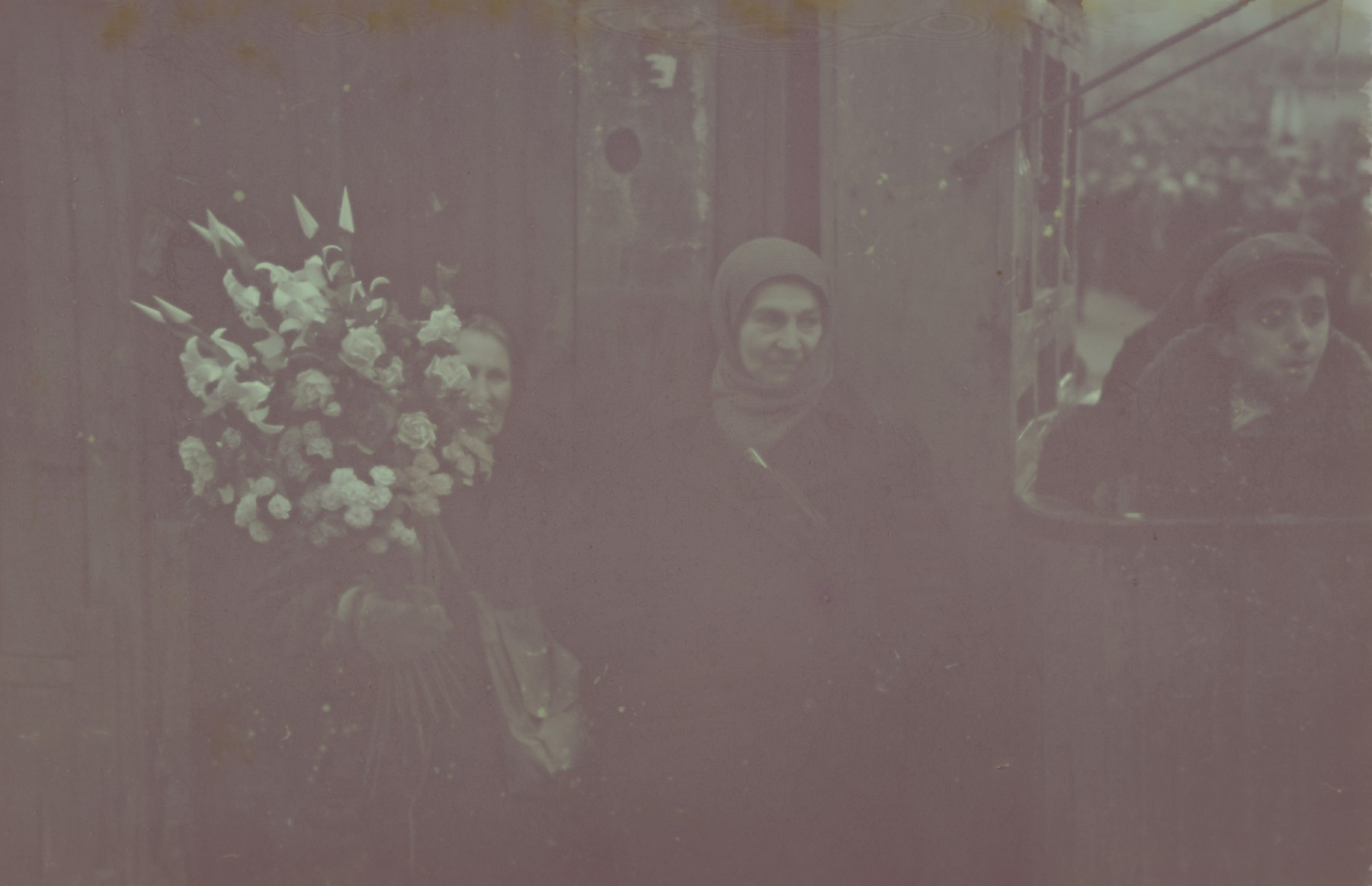 Two women stand next to wreaths of flowers probably in or near Lodz.