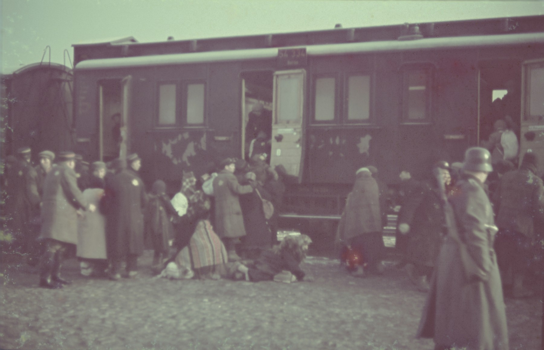 "Jews board a passenger train during a deportation action in the Lodz ghetto.  Original German caption: ""Judenaussiedlung"" (Jewish resettlement), April 1942, #132."