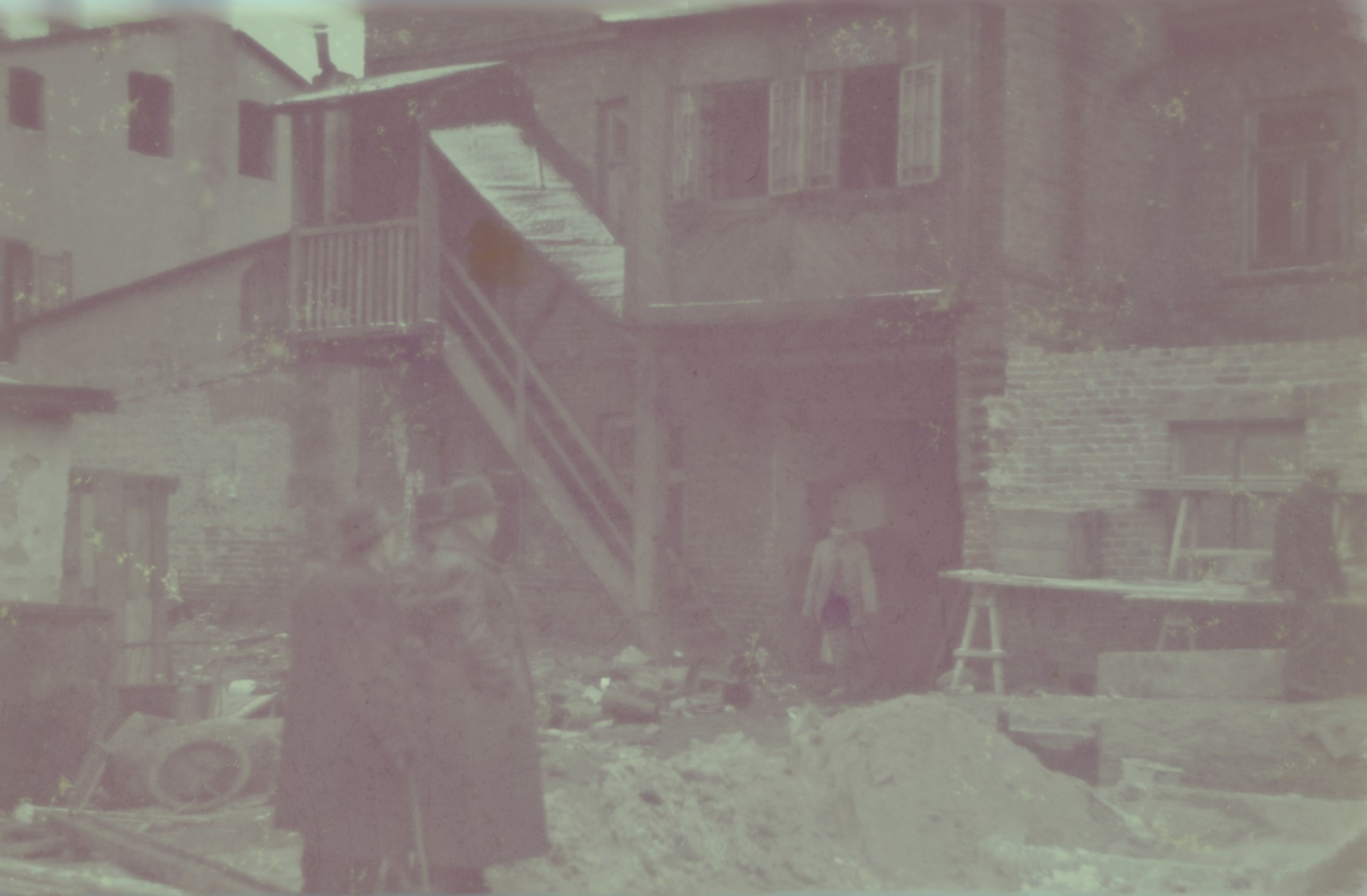 Two men survey a pile of rubble outside a building in the Lodz ghetto.