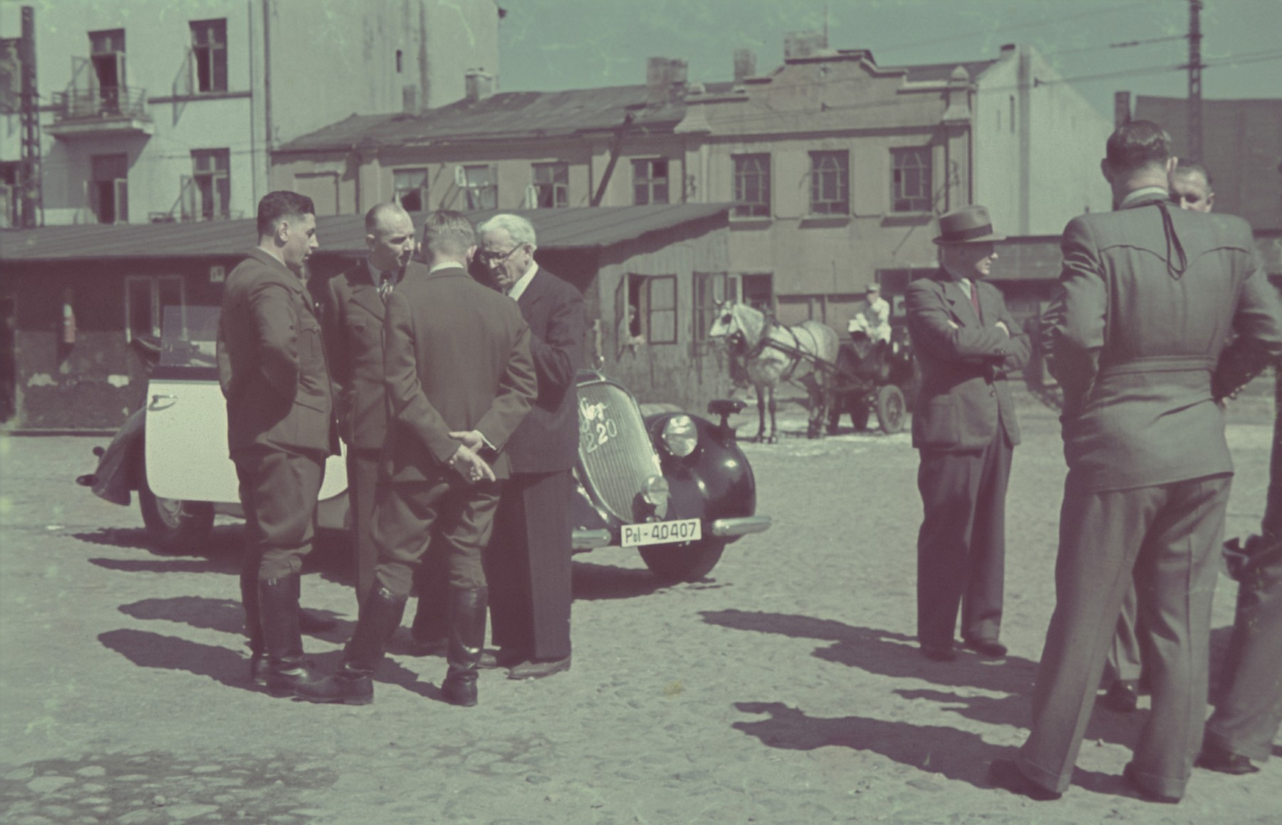 Mordechai Rumkowski meets with German officials on a street of the Lodz ghetto.  Original German caption:#163.