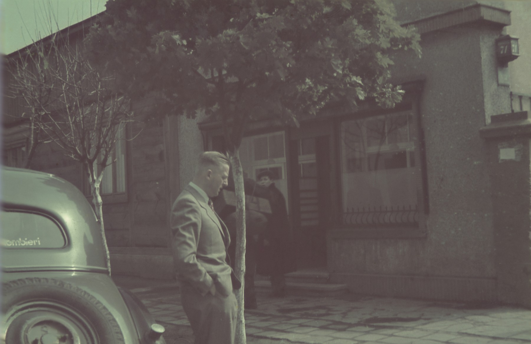 Hans Biebow stands next to an automobile on a street scene in the Lodz ghetto.