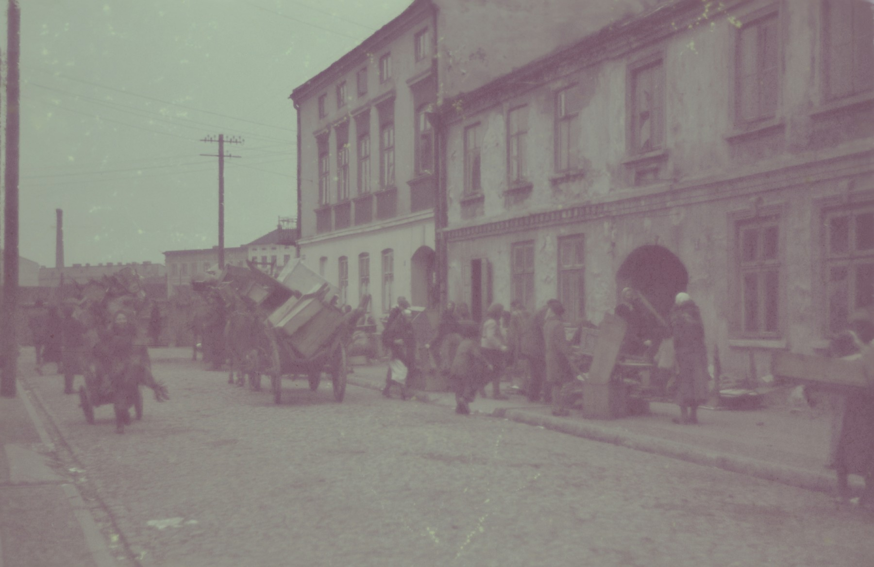Horse-drawn wagons carry the belongings of Jews moving into the Lodz ghetto.