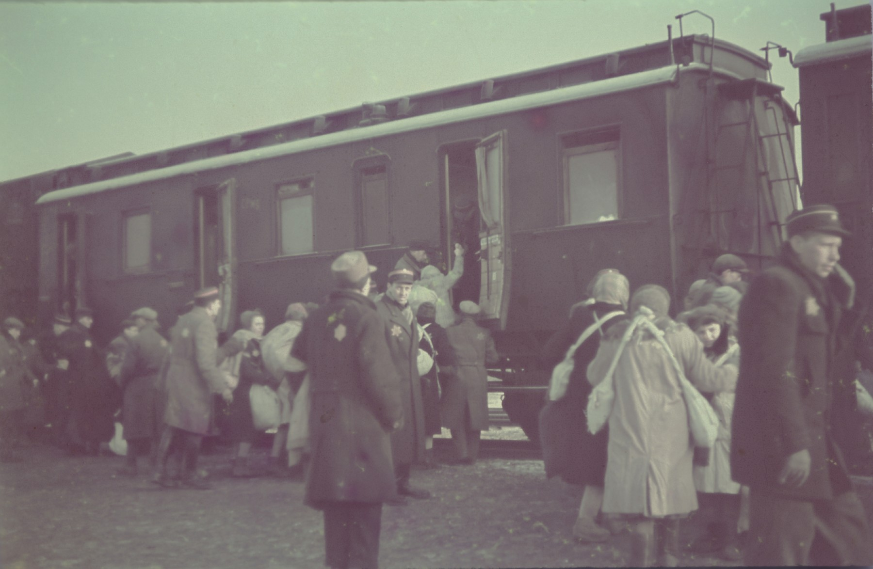 """Jews board a passenger train during a deportation action in the Lodz ghetto.  Original German caption: """"Judenaussiedlung"""" (Resettlement of Jews), April 1942, #131."""