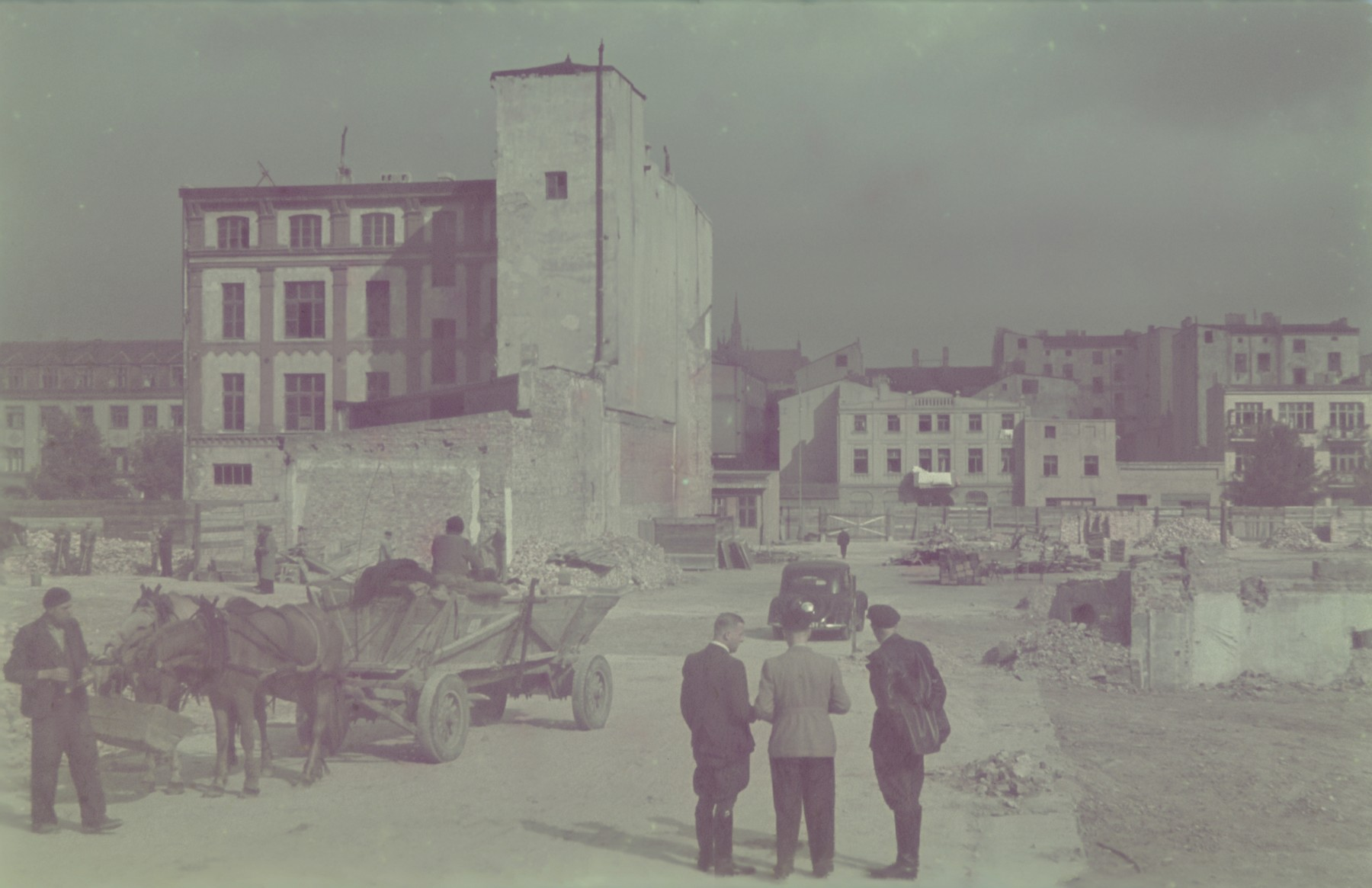"Hans Biebow and two other men survey a partially destroyed street in the Lodz ghetto.  Original German caption: ""...aktion"" #171 (number 160 was crossed out)"