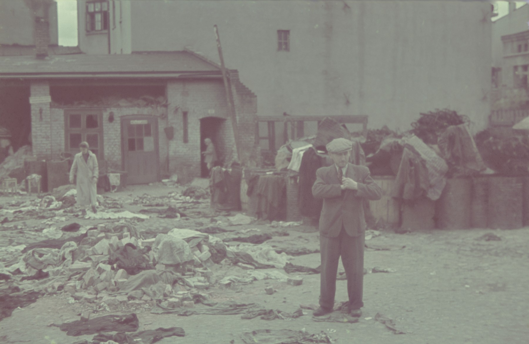 Two men walk through a courtyard strewn with rags in what [probably is a workshop in the Lodz ghetto].