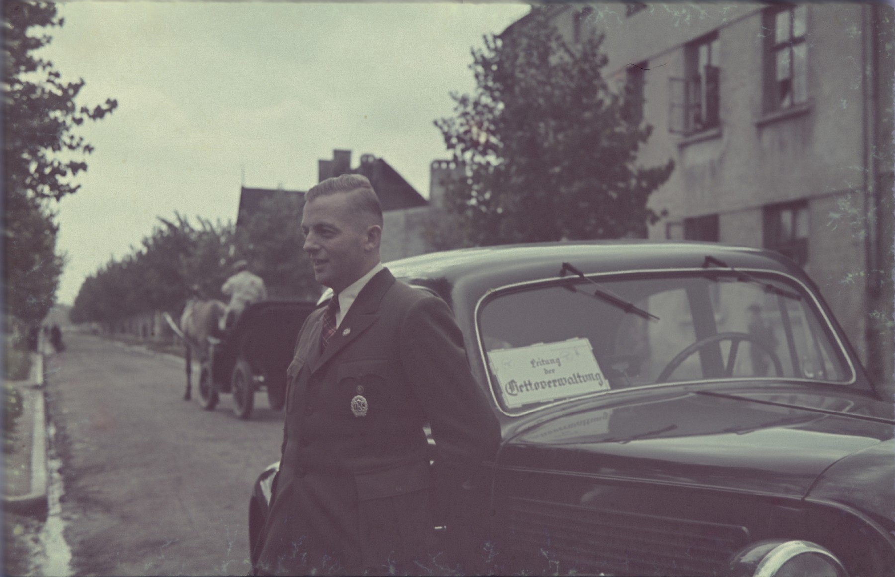 """Hans Biebow, the Nazi administrator of  the Lodz ghetto,  poses in front of a car in the Lodz ghetto.  Original German caption: """"Herr Biebow"""" (Mr. Biebow), #155."""