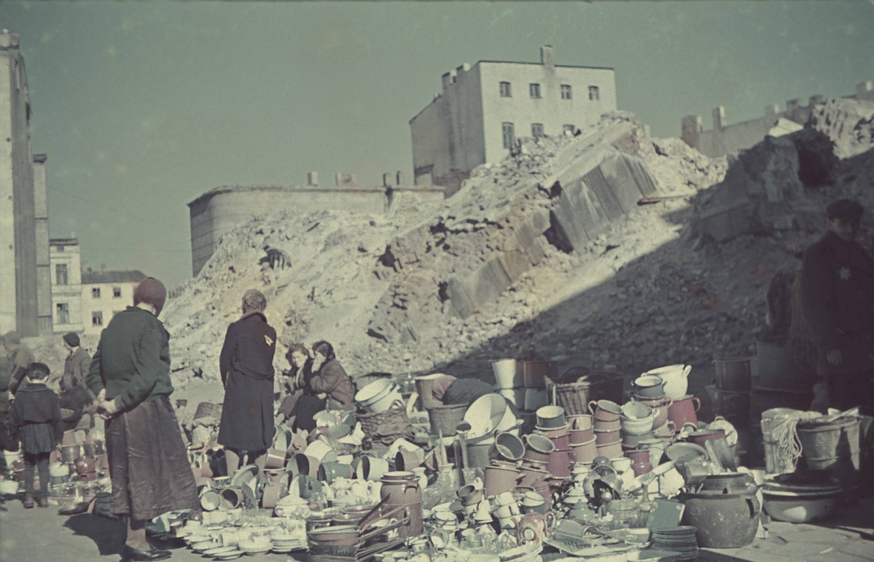"""Jewish women inspect old pots and crockery in [what probably is a market] in the Lodz ghetto.  Original German caption: """"Strassenbild"""" (street scene), #53."""