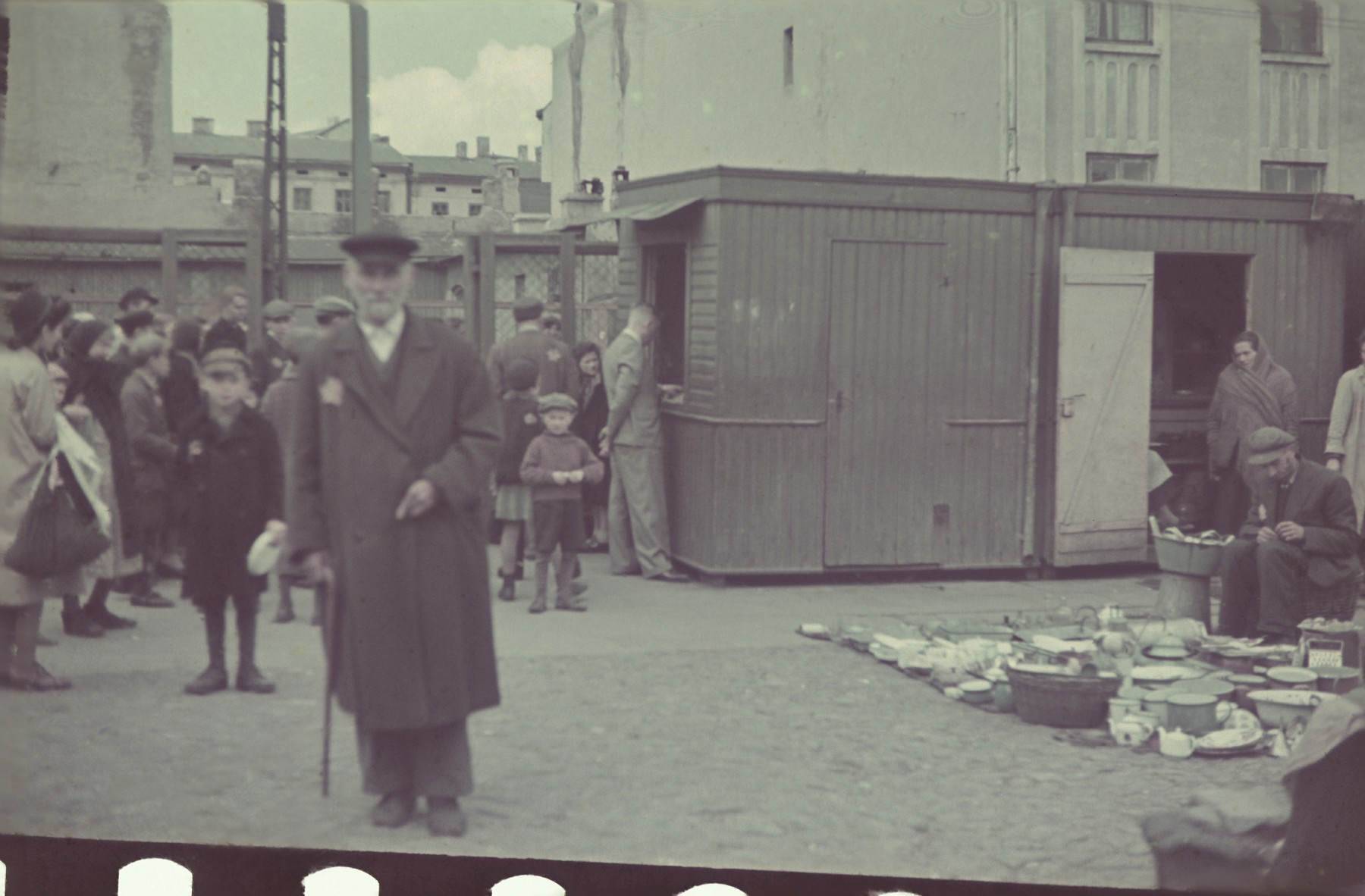 An elderly man  carrying a cane poses in the market in the Lodz ghetto.