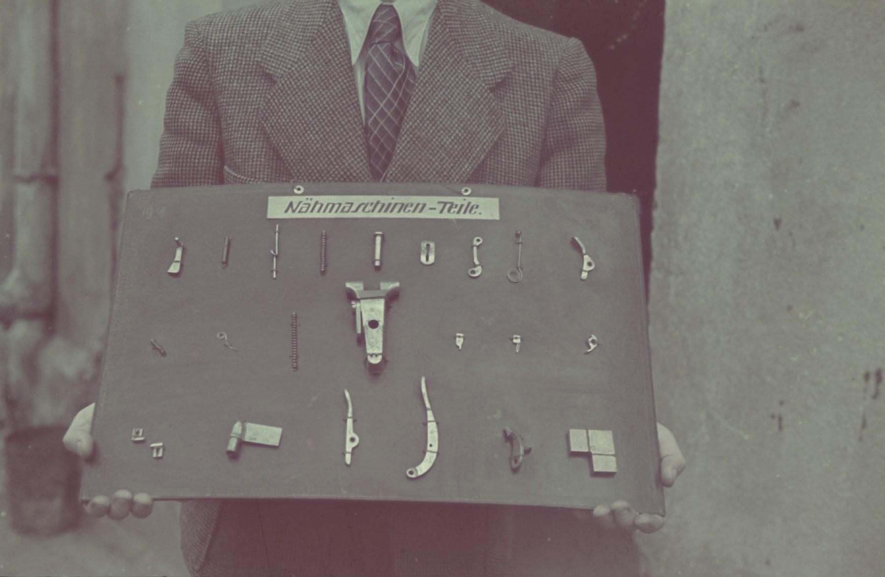 """A man holds a display of sewing machine parts in the Lodz ghetto.  Original German caption: """"Getto Litzmanndstadt, Aus der Feinmechanik (fine mechanics), #18."""