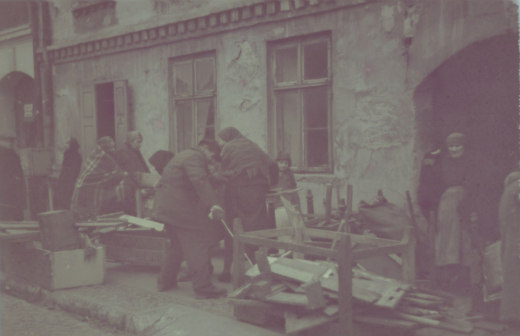 Jews haul old furniture down a sidewalk in the Lodz ghetto.