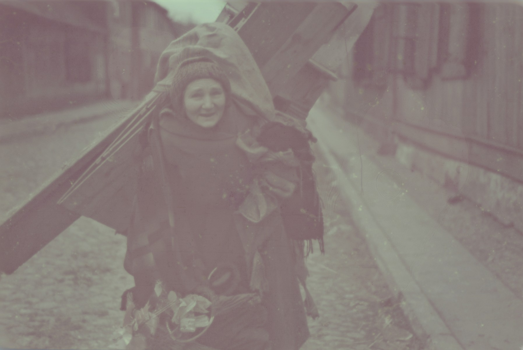 A Jewish woman carries large bundles and wooden planks on her back while walking down a street in the Lodz ghetto.