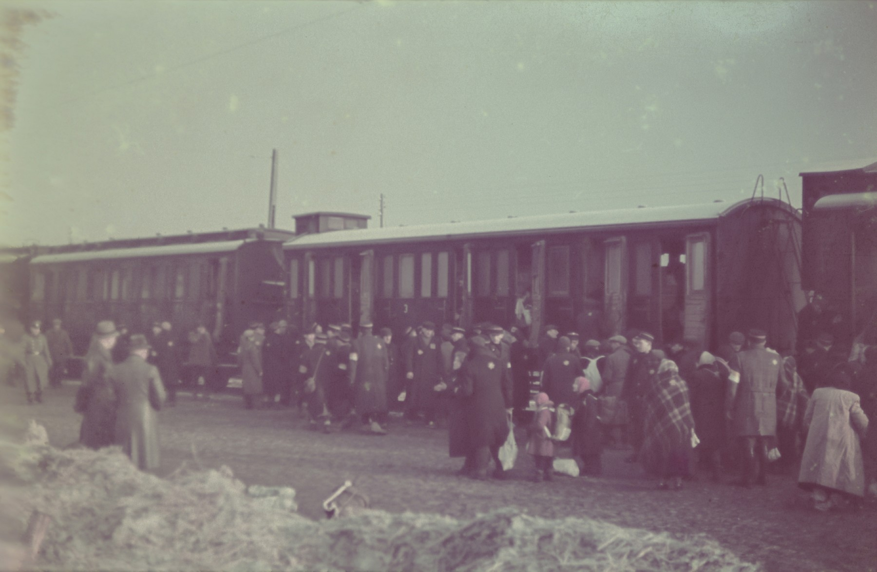 """Jews board a passenger train during a deportation action in the Lodz ghetto.  Original German caption: """"Judenaussiedlung"""" (Jewish resettlement), April 1942, #134."""