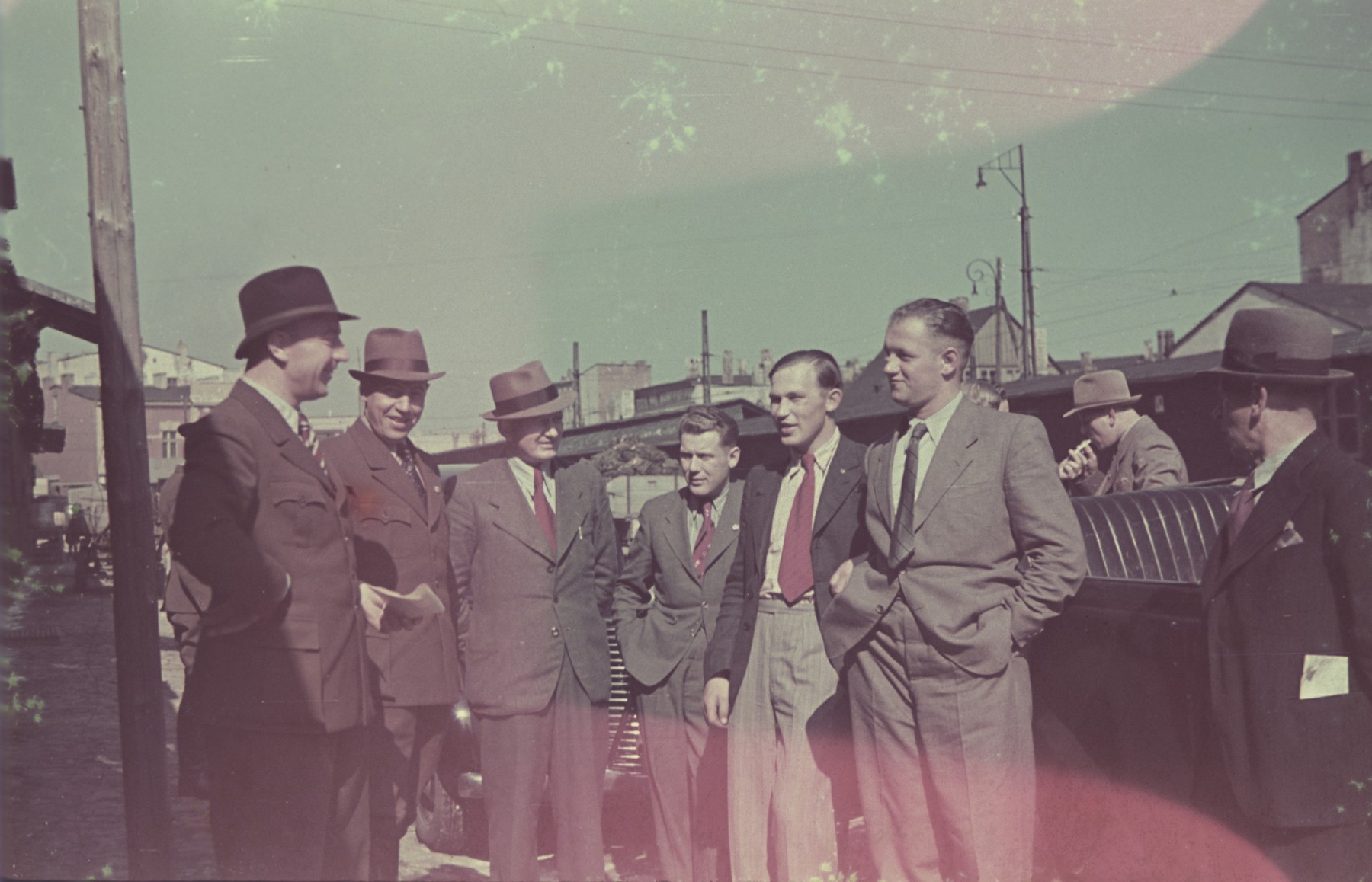 A group of men gather on a street probably in or near Lodz.