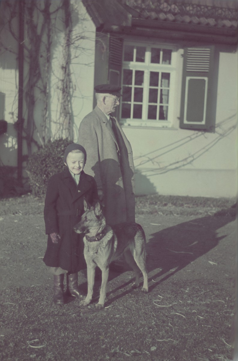 Mr. Meir, father-in-law of Hans Biebow, walks with one of the sons of Hans Biebow, outside their home in Bremen, Germany.