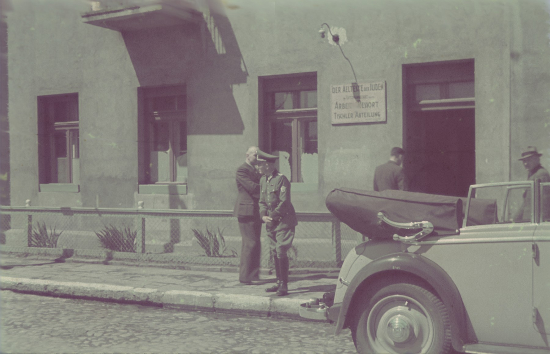 "German military personnel stand outside carpentry workshop in the Lodz ghetto.  Original German caption: ""Litzmannstadt-getto, Tischlerei"" (carpentry workshop), #1."