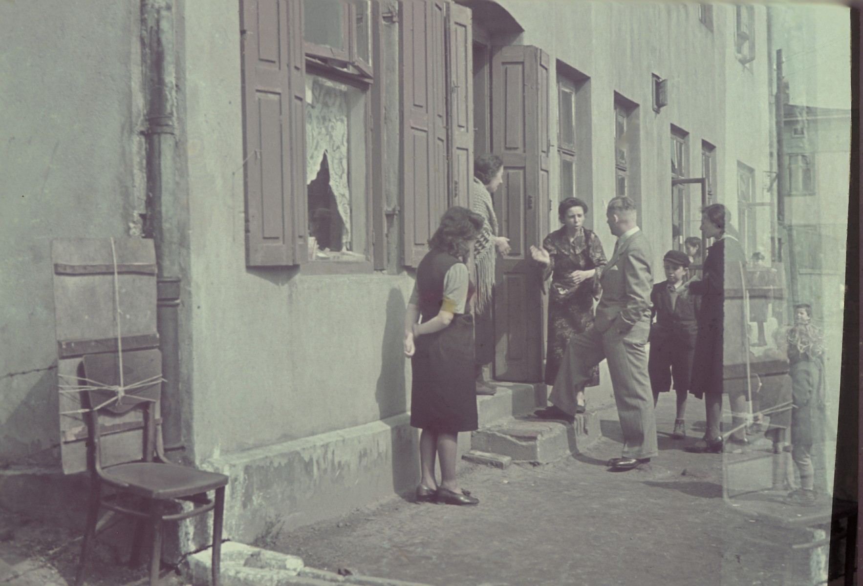 A German official [probably Biebow] talks to Jewish women in the doorway to their home in the Lodz ghetto.