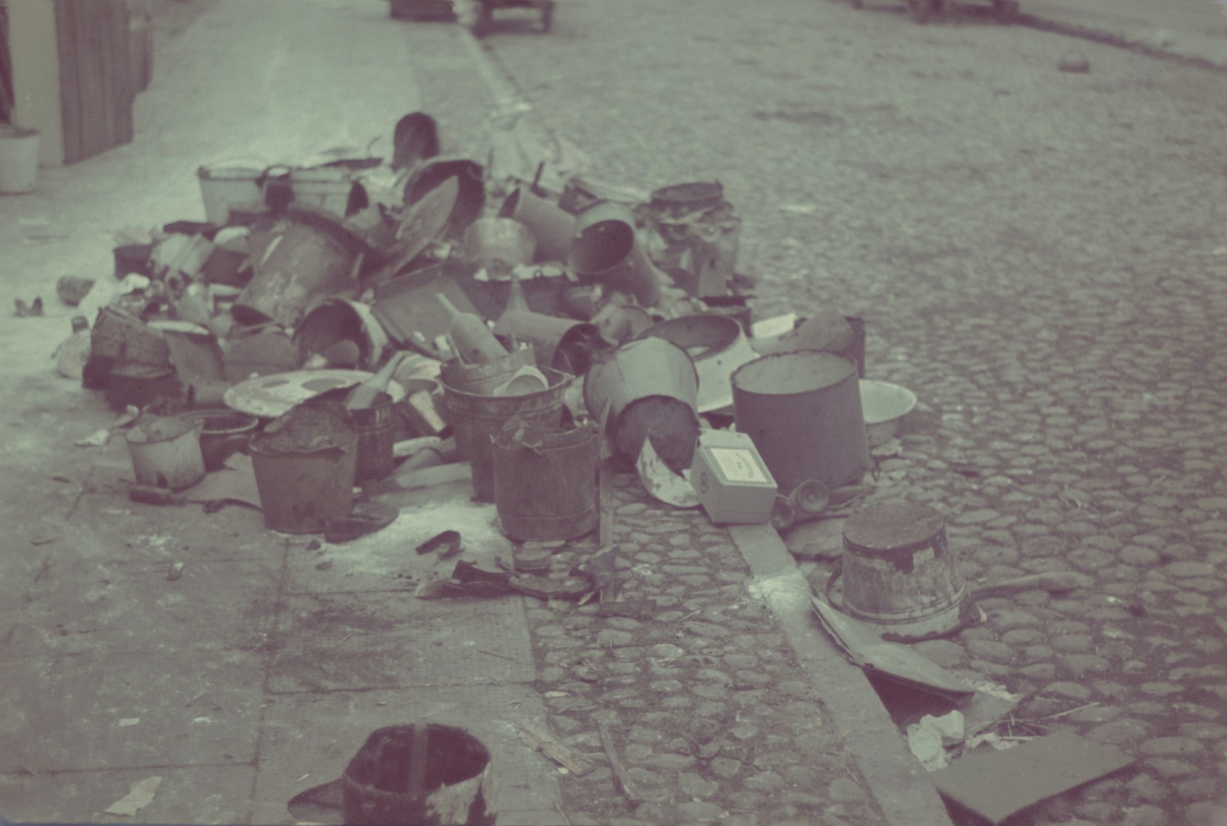Discarded buckets and other personal belongings lies in a pile on a street of the Lodz ghetto.