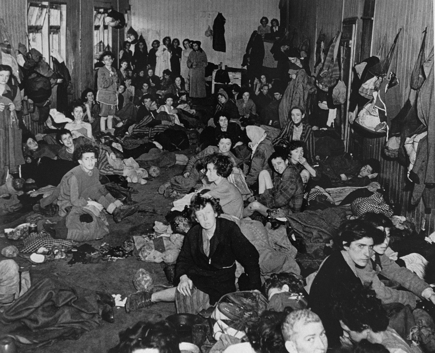 "Female survivors in the ""Gypsy barracks"" after liberation.   The original caption reads: ""A view of the interior of one of the huts."""