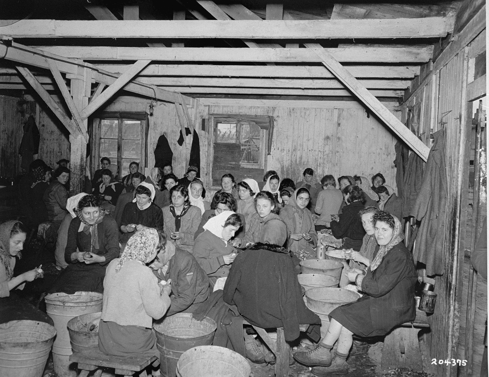 Female survivors peel potatoes in a  barracks in the Bergen-Belsen concentration camp.