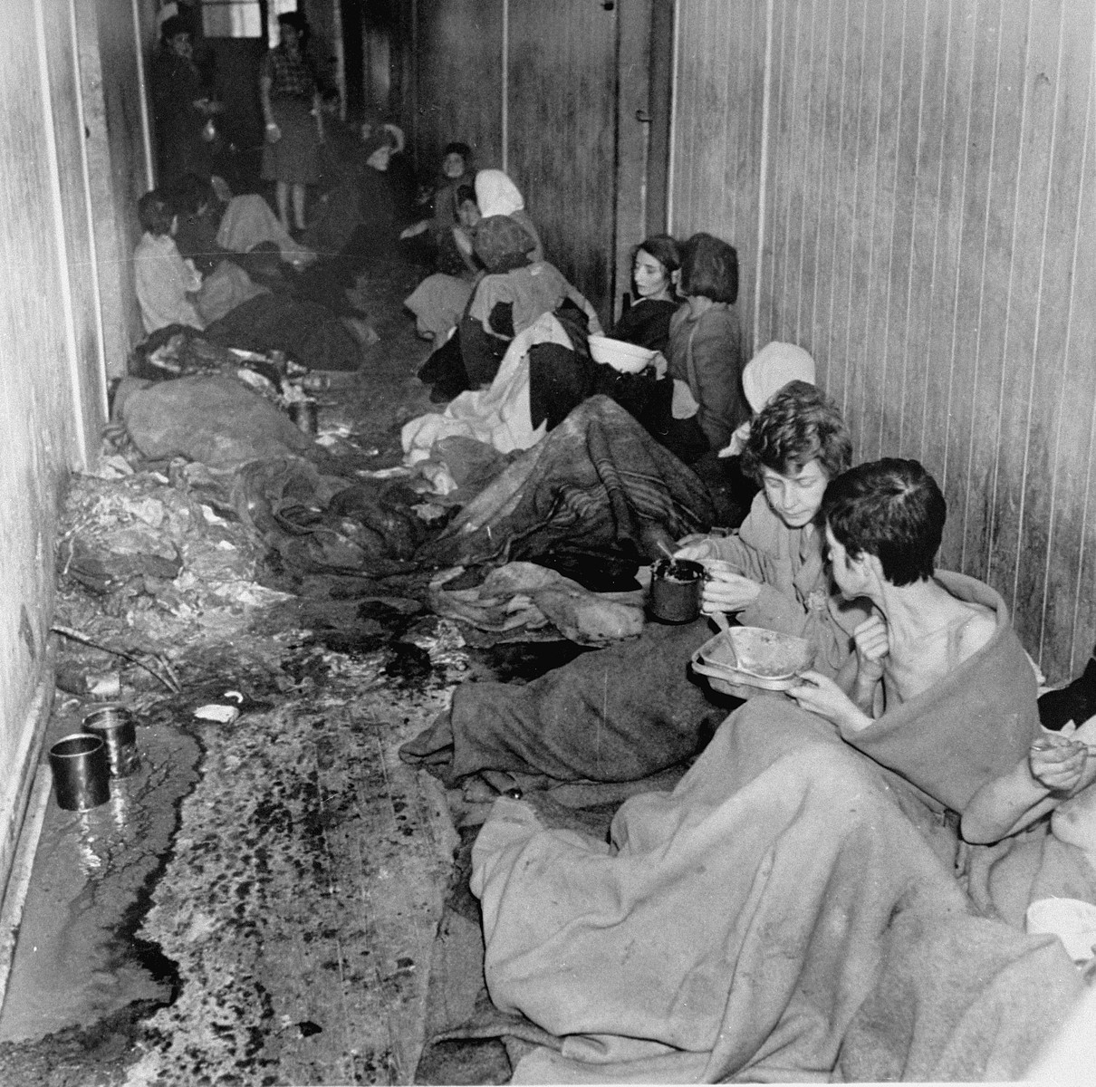 "Female survivors inside a squalid barracks in Bergen-Belsen after liberation.  The original caption reads: ""Squalid conditons still exist in some parts of the camp which will be cleared up in a few days."""